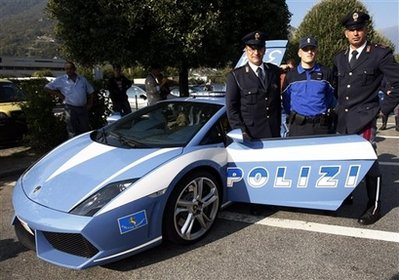 Two officers of Italian police, left and right, and their Swiss colleague pose near a Lamborghini Gallardo of Italian traffic police 'Polizia stradale', which is told to be the world's fastest police car, at a highway rest area in Bellinzona, southern Switzerland, Wednesday, Oct. 7, 2009. The Lamborghini will be presented at an international police meeting in the Netherlands. (AP Photo/Keystone/Kar